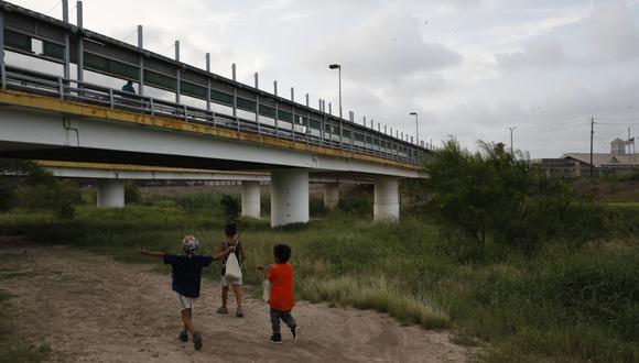 En esta fotografía de archivo del 26 de junio de 2019, niños migrantes caminan con sus familias a lo largo del Río Grande, mientras los peatones usan el puente Puerta México para ingresar a Brownsville, Texas. (AP/Rebecca Blackwell)