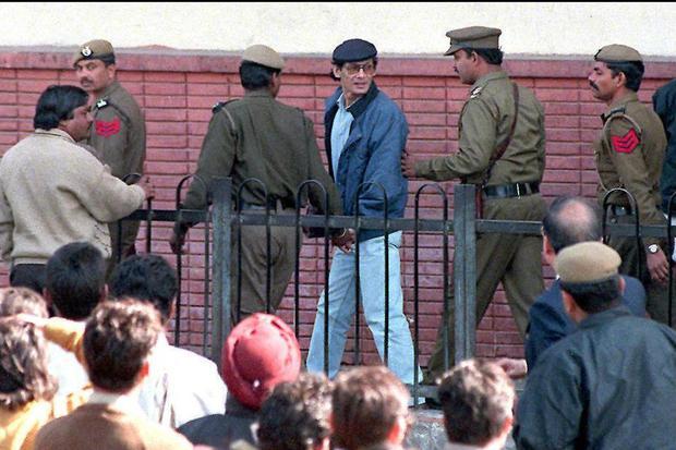 La policía escolta a Charles Sobhraj a un tribunal de Nueva Delhi el 12 de febrero, donde debe defender su liberación de la cárcel mientras los transeúntes curiosos lo observan. (Foto: Ravi Raveendran / AFP)
