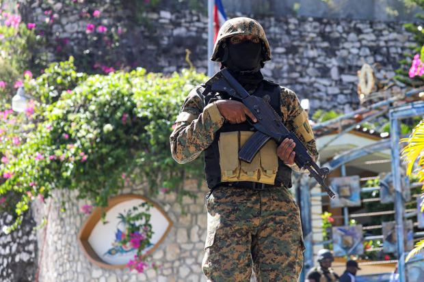 A policeman is in custody outside the home of the Haitian Jowanel Mois, who was assassinated on July 7, 2021 in Port-au-Prince.  (Photo by VALERIE BAERISWYL / AFP).