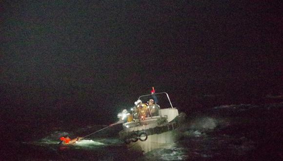 Esta fotografía tomada el 2 de septiembre de 2020 muestra a los guardacostas rescatando a un hombre filipino en la isla de Amami Oshima, sobreviviente del buque de carga que naufragó con 43 personas cerca de Japón. (10th Regional Coast Guard Headquarters / AFP)