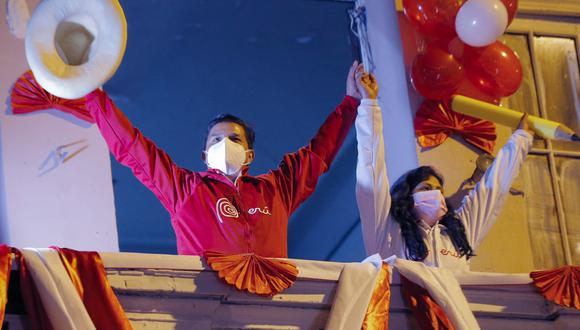 Peruvian leftist presidential candidate Pedro Castillo (L) and his wife Liliana Paredes waves supporters from a balcony at his campaign headquarters during his closing rally in Lima on June 3, 2021, ahead of the June 6 runoff election against right-wing candidate Keiko Fujimori. (Photo by Luka GONZALES / AFP)