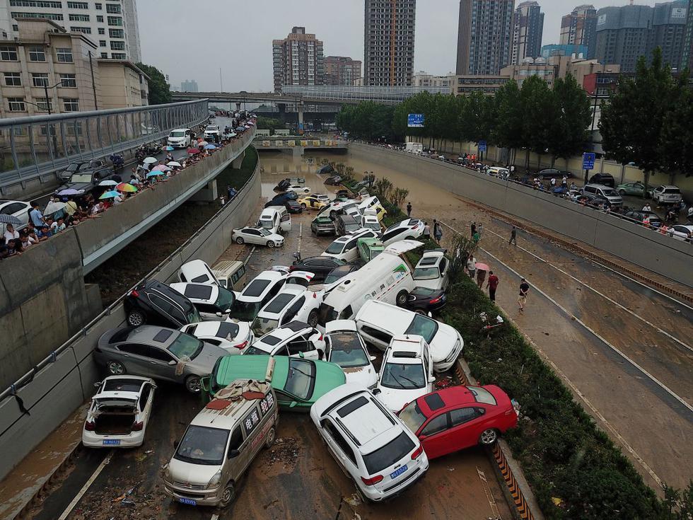 Una vista aérea muestra automóviles arrastrados por la inundación hasta la entrada de un túnel después de que las fuertes lluvias azotaran la ciudad de Zhengzhou, en la provincia central china de Henan. (Foto de Noel Celis / AFP).