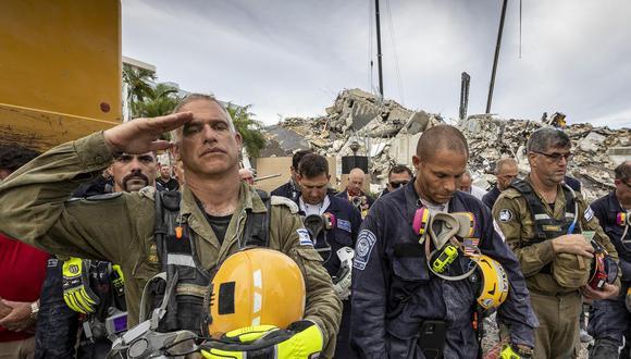 Un miembro del equipo de búsqueda y rescate israelí saluda cerca a los escombros de lo que alguna vez fue el Champlain Towers South durante un momento de oración y silencio en Surfside, Florida, el 7 de julio de 2021. (Jose A. IGLESIAS / POOL / AFP).