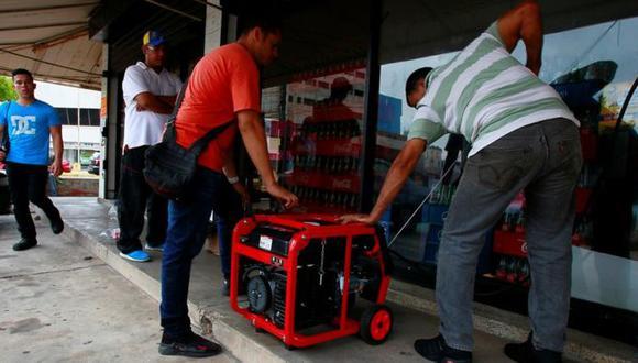 Dos hombre tratan de encender un generador frente a un supermercado de Maracaibo. Foto: Reuters