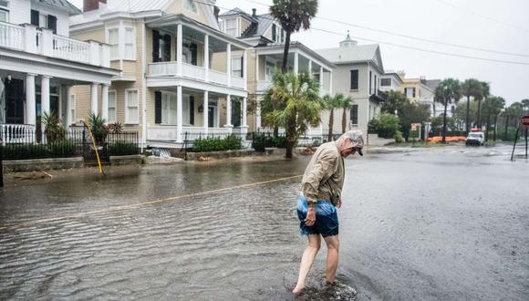 Un hombre camina por South Battery St. mientras limpia los escombros de los desagües pluviales el 5 de septiembre de 2019 en Charleston. (Foto: AFP).