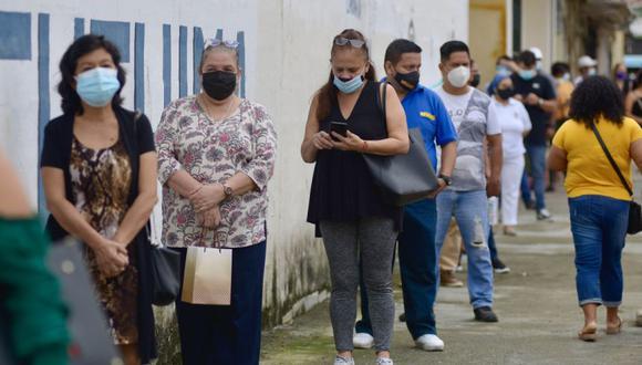 Varias personas acuden a un centro de votación en el colegio Calicuchima con doble mascarilla y un visor para protegerse del covid-19, en Guayaquil (Ecuador). (Foto: EFE/ Marcos Pin).