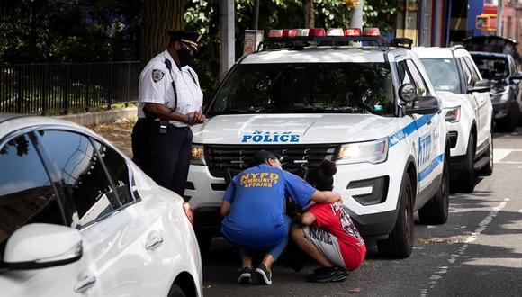 Los oficiales de policía de la ciudad de Nueva York consuelan a una mujer que conocía a un hombre de 27 años que fue encontrado muerto a tiros en un parque en el barrio de Crown Heights de Brooklyn, Nueva York. (EFE / EPA / JUSTIN LANE).