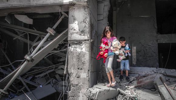 Niños palestinos rescatan juguetes de su casa dañada en la Torre Al-Jawhara en la ciudad de Gaza, el 17 de mayo de 2021. (Foto de ANAS BABA / AFP).