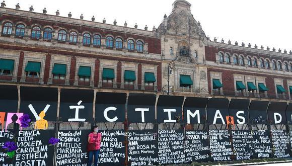 Una mujer se para junto a carteles con nombres de víctimas por feminicidios en un cerco metálico instalado para proteger el Palacio Nacional de México. (Foto: EFE/Carlos Ramírez).