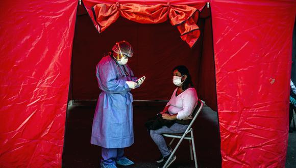 Estudio de la Universidad de Washington advierte sobre dramática proyección para el Perú sobre el coronavirus. En la imagen, personal sanitario hace una prueba de descarte de Covid-19 en el mercado de Ciudad de Dios, en el sur de Lima. (Foto: ERNESTO BENAVIDES / AFP).