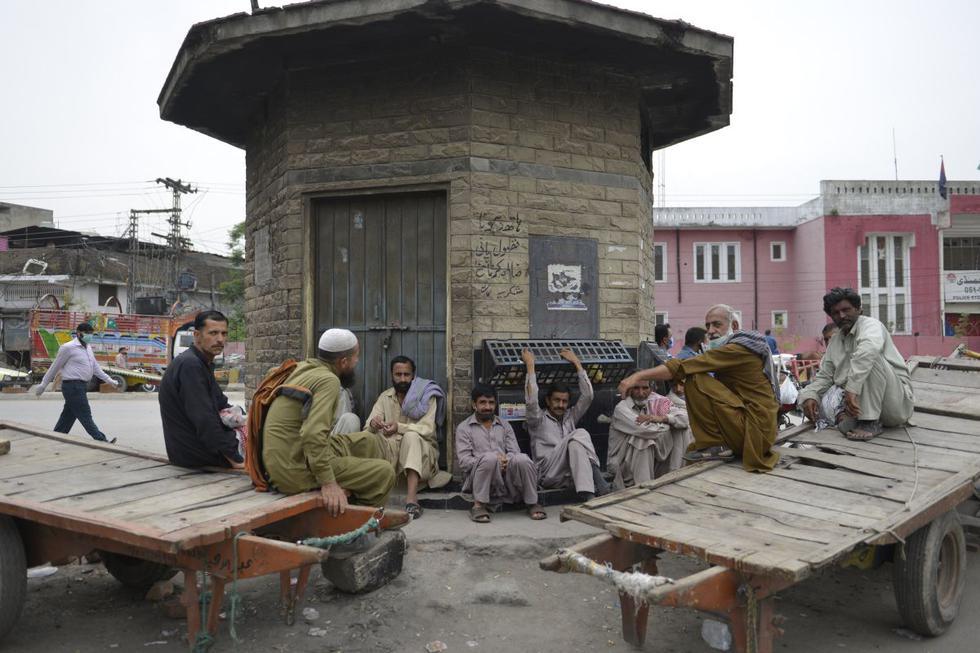 Trabajadores se sientan en la carretera durante un bloqueo nacional impuesto por el gobierno como medida preventiva contra el coronavirus, en Rawalpindi. (Foto: AFP/Farooq Naeem)