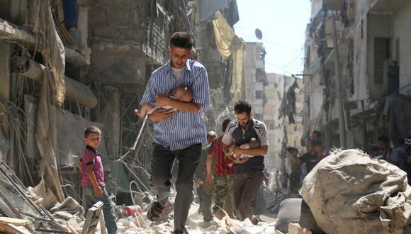 En esta foto de archivo tomada el 11 de septiembre de 2016, hombres sirios que llevan bebés se abren paso entre los escombros de edificios destruidos luego de un ataque aéreo en el barrio de Salihin, controlado por los rebeldes, en la ciudad norteña de Alepo. (Foto de Ameer al-HALBI / AFP).