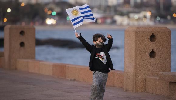 Un niño con una mascarilla ondea una bandera nacional uruguaya mientras juega en el paseo marítimo de Montevideo. (Foto: AP)