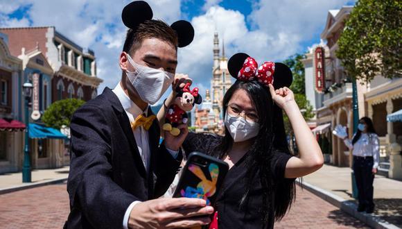Los visitantes vestidos con disfraces se toman una selfie en Disneyland de Hong Kong el 18 de junio de 2020, después de que el parque temático reabriera tras casi cinco meses de cierre por el coronavirus. (Foto por Anthony WALLACE / AFP).