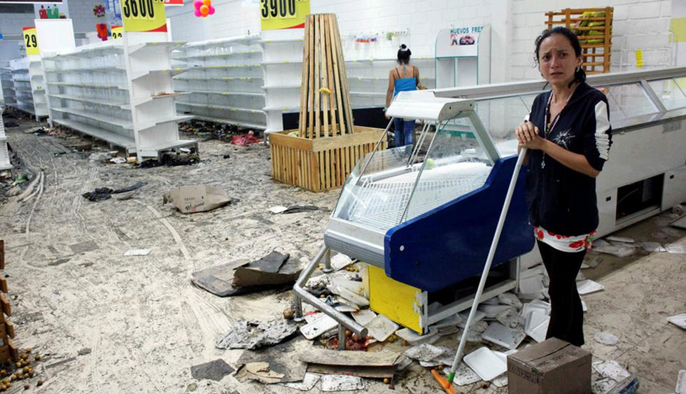 Workers clean the floor next to empty shelves and refrigerators in a supermarket after it was looted in San Cristobal, Venezuela May 17, 2017. REUTERS/Carlos Eduardo Ramirez     TPX IMAGES OF THE DAY