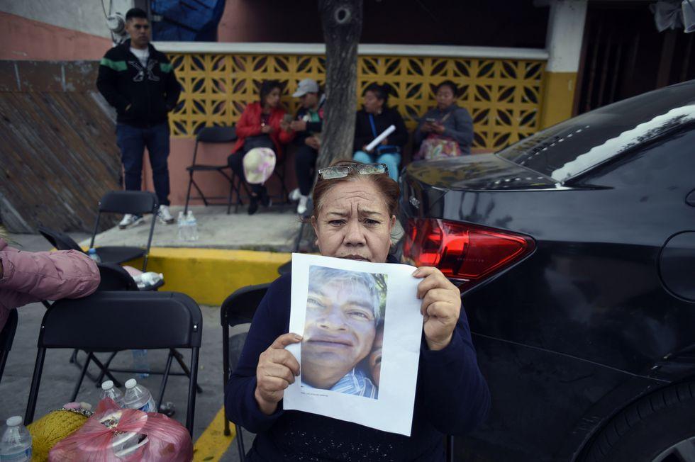 Una mujer muestra la foto de un pariente desaparecido tras la explosión. (AFP).