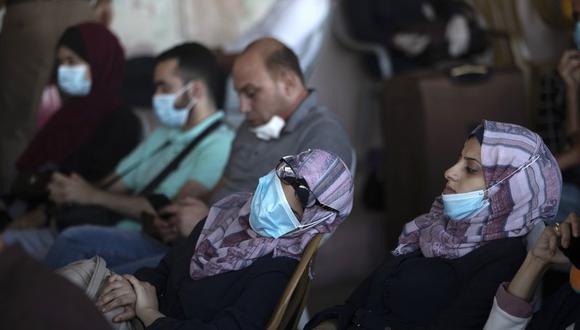 Fotografía de archivo del 27 de septiembre de 2020 de palestinos con mascarillas sentados junto a su equipaje mientras esperan cruzar el cruce fronterizo con Egipto Rafah en el sur de la Franja de Gaza. (AP Foto/Khalil Hamra, Archivo).