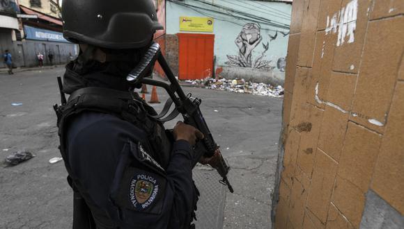 Un miembro de la Policía Nacional Bolivariana monta guardia en una esquina durante un enfrentamiento con presuntas bandas criminales en el barrio La Vega de Caracas el 24 de mayo de 2021. (Foto de Yuri CORTEZ / AFP).