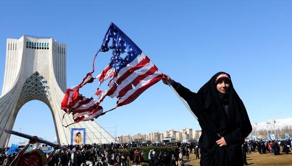 Una iraní ondea una bandera estadounidense quemada durante las conmemoraciones de los 41 años de la Revolución Islámica el 11 de febrero del 2020. (Foto por ATTA KENARE / AFP).