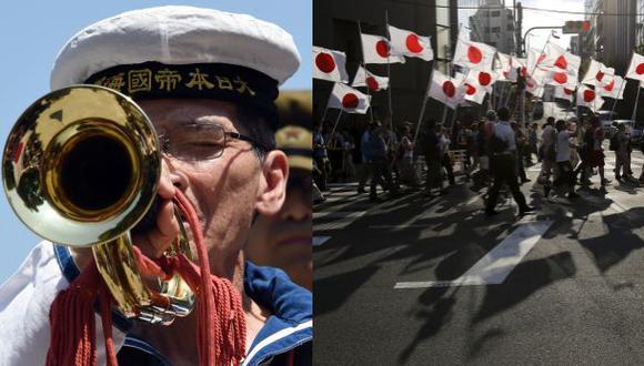 """Los miembros del movimiento nacionalista """"Ganbare Nippon"""" (derecha) sostienen banderas nacionales japoneses mientras marchan cerca del santuario Yasukuni, que hace un tributo a las víctimas de guerra en Tokio, en el 70 aniversario de la"""