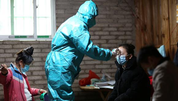 Un médico que usa traje de protección toma la temperatura corporal a una aldeana en Danzhai, China. (Reuters).