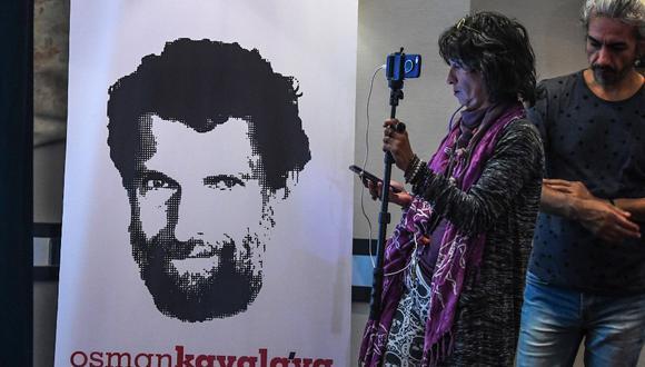 Un periodista se para frente a un cartel con el empresario y filántropo encarcelado Osman Kavala durante una conferencia de prensa de sus abogados en octubre de 2018. En ese entonces, Kavala cumplía un año arrestado por las autoridades turcas. (OZAN KOSE / AFP)