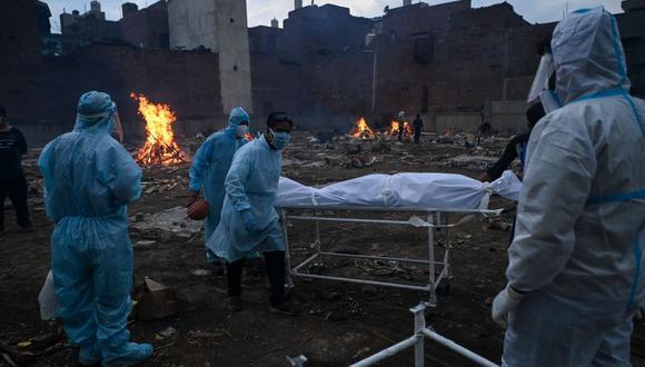 Familiares con trajes de equipo de protección personal llevan el cuerpo de una persona que murió debido al coronavirus Covid-19 en un crematorio en Nueva Delhi, India. (Foto de Prakash SINGH / AFP).