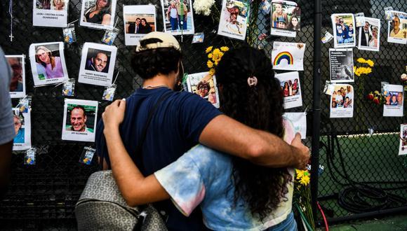 La gente visita el memorial improvisado para las víctimas del derrumbe del edificio en Surfside, Florida, al norte de Miami Beach. (Foto: CHANDAN KHANNA / AFP).