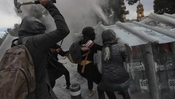 Mujeres activistas usan martillos para enfrentarse con la policía en las afueras del Palacio Nacional de México. (EFE/Sáshenka Gutiérrez).