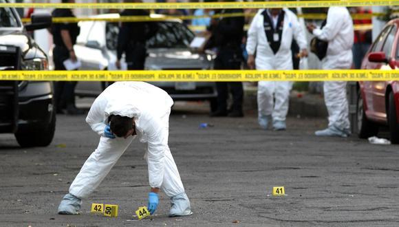 imagen referencial muestra a unos peritos trabajando en la escena de un crimen. (AFP)