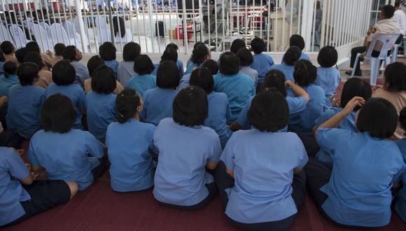 En esta foto de archivo tomada el 8 de febrero de 2018, los reclusos se sientan juntos para asistir a un programa especial de entretenimiento en una prisión en la provincia central tailandesa de Nakhon Nayok. (LILLIAN SUWANRUMPHA / AFP).