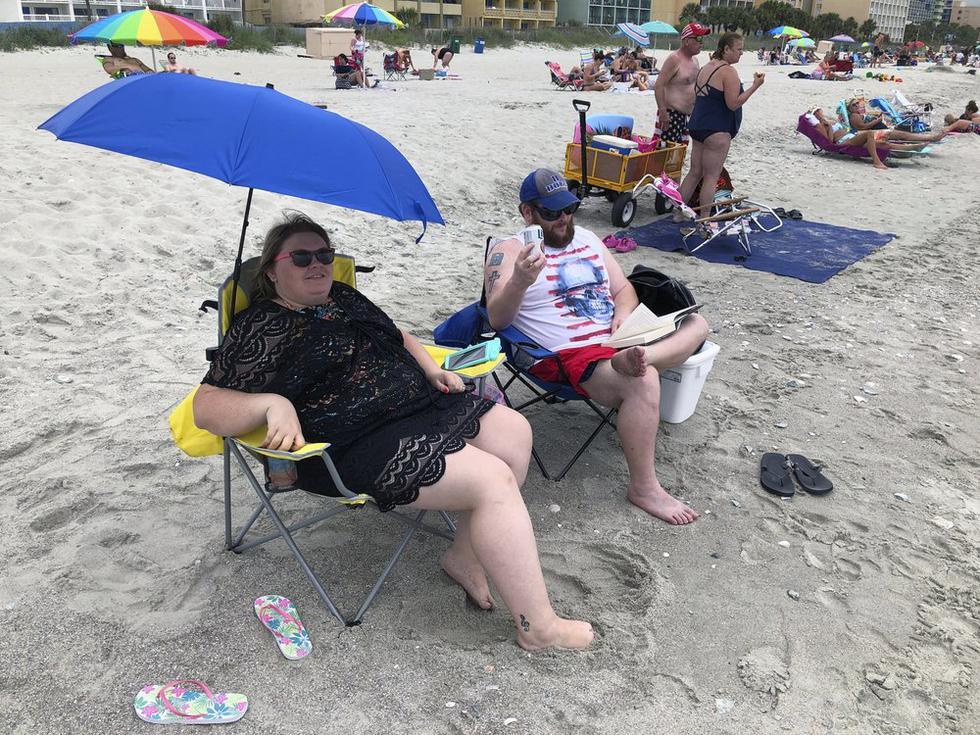 Tabatha Johnson, a la izquierda, y su esposo, Mark, disfrutan de su primer día de vacaciones en Myrtle Beach, Carolina del Sur. (Foto: AP/Jeffrey Collins)