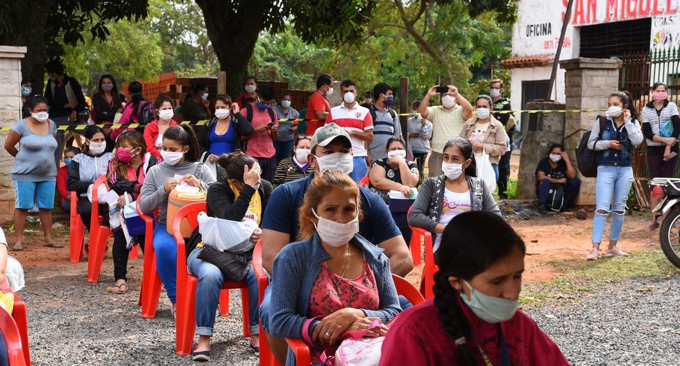 Las personas que usan máscaras faciales esperan un plato de comida mientras los voluntarios la preparan en el comedor popular más grande de Paraguay con la intención de alimentar a unos 7.000 ciudadanos vulnerables durante la pandemia de coronavirus COVID-19. (Foto por Norberto DUARTE / AFP).