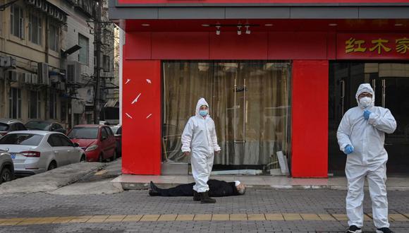 Esta foto tomada el 30 de enero de 2020 muestra a funcionarios con trajes protectores cerca de un anciano que se derrumbó y murió en una calle de Wuhan, China, en medio de la pandemia de coronavirus. (Foto de Hector RETAMAL / AFP).