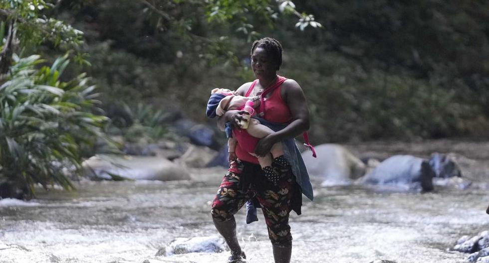 Una mujer migrante cruza el río Acandí con un niño en brazos, en Acandí, Colombia, el miércoles 15 de septiembre de 2021. (AP Foto/Fernando Vergara).