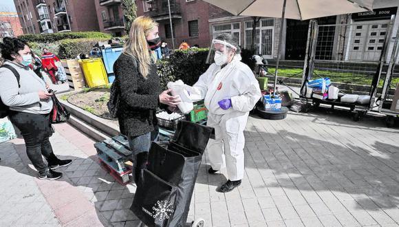 Gente recibiendo alimentos en un barrio de Madrid por parte de un grupo de ayuda humanitaria. (Foto: Getty Images /El Tiempo de Colombia, vía GDA).