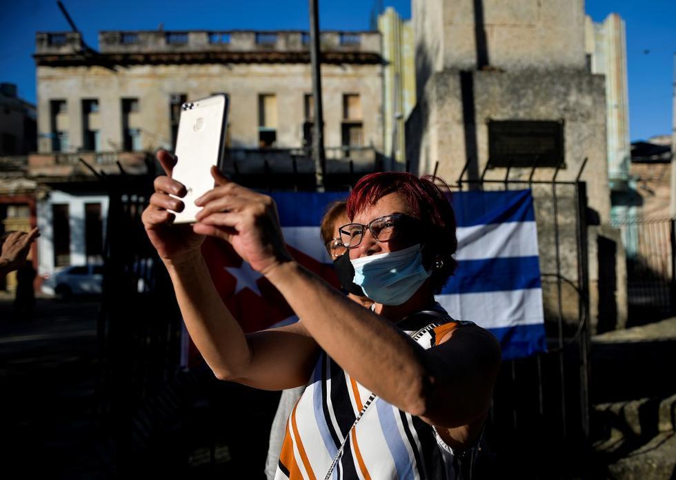 Una mujer simpatizante del presidente cubano Miguel Díaz-Canel, participan en un concierto de concentración para condenar la supuesta campaña mediática en apoyo al movimiento San Isidro. (YAMIL LAGE / AFP).