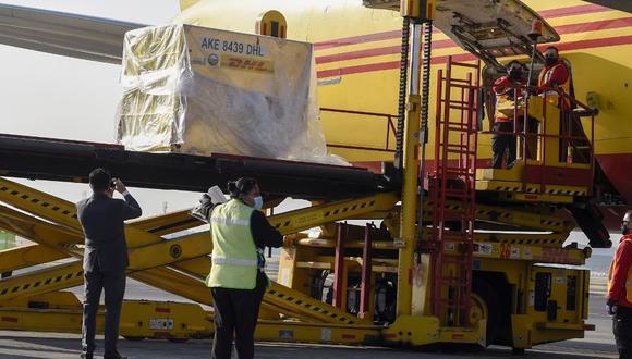 Empleados descargan contenedores de envío de la vacuna Pfizer Covid-19 desde un avión de la empresa de mensajería internacional DHL, en el Aeropuerto Internacional Benito Juárez de la Ciudad de México. (Foto: ALFREDO ESTRELLA / AFP)
