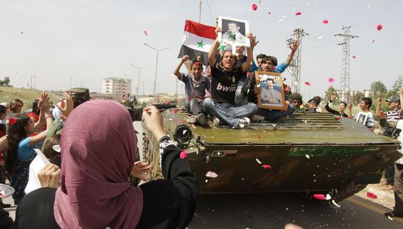 En esta foto del 5 de mayo de 2011, mujeres sirias vitorean a las tropas del ejército que salen del de Daraa, epicentro de la Primavera Árabe en Siria. (Foto de Louai Beshara / AFP).