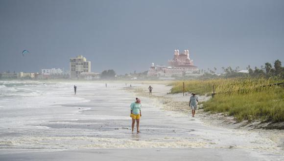 Unas personas caminan por la playa Pass-a-Grille tras el paso de la tormenta Elsa en Tampa Bay, Florida, el 7 de julio de 2021. (Martha Asencio-Rhine/Tampa Bay Times via AP).