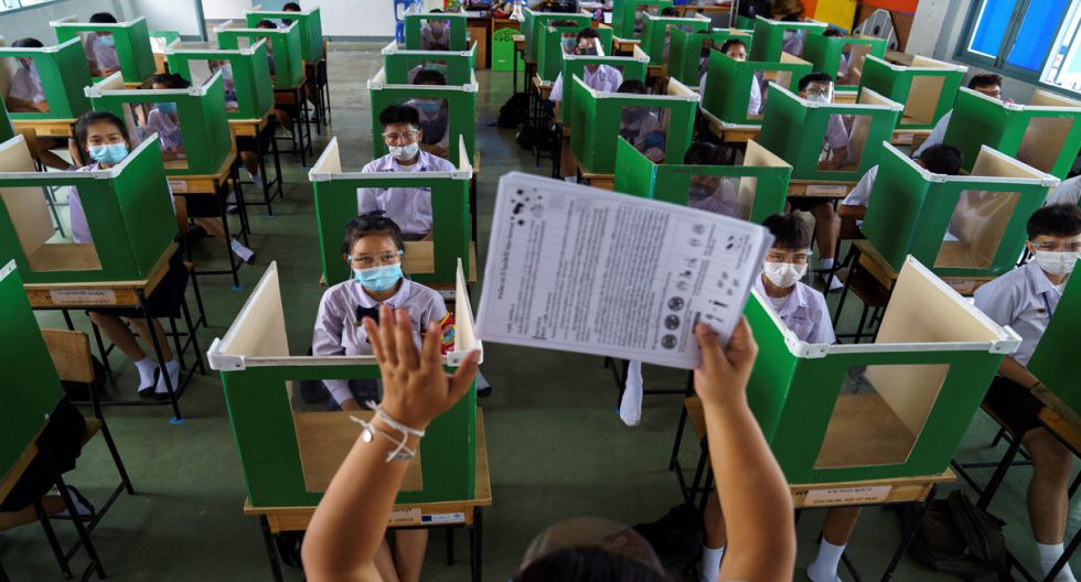 Alumnos del colegio Sam Khok, de la provincia Pathum Thani, en Tailandia, con mascarillas y protectores faciales protegidos por urnas reutilizadas mientras asisten a una clase después de que el gobierno anunciara la reapertura de las escuelas. (Foto: Reuters)