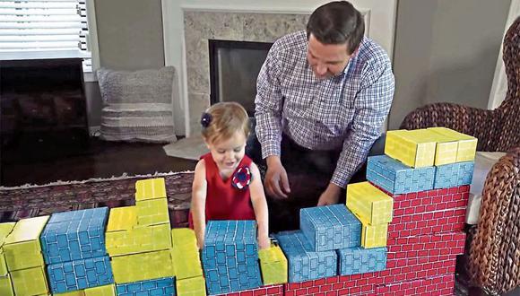"""El aspirante a gobernador en Florida Ron DeSantis, del Partido Republicano, enseña a su hija a """"construir""""un muro en un vídeo de su campaña."""