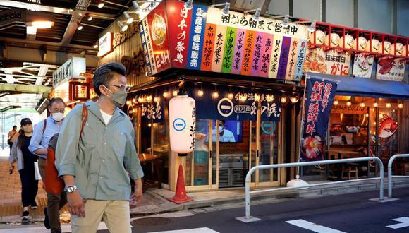Los transeúntes pasan frente a un restaurante en Tokio, Japón, el 17 de junio de 2021, día en que el gobierno decidió levantar en nueve prefecturas el estado de emergencia por coronavirus COVID-19. (EFE / EPA / FRANCK ROBICHON).