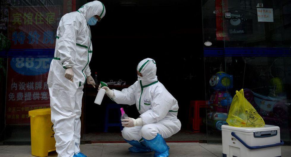 Un trabajador médico que usa un traje de materiales peligrosos desinfecta a un colega en una clínica de pruebas para el nuevo coronavirus en Wuhan, en la provincia central de Hubei de China. (Foto: AFP/Noel Celis)