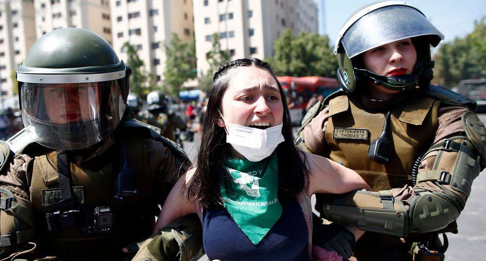La policía detiene a una mujer durante una protesta en el centro de Santiago. (AFP / Pablo VERA).