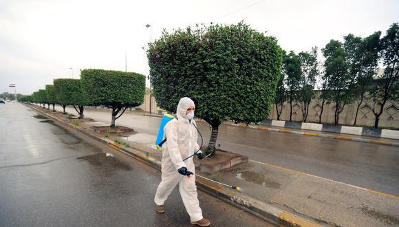 Un soldado iraquí con un traje protector rocía con desinfectante una calle de Bagdad. (Foto: Thaier Al-Sudani / Reuters)
