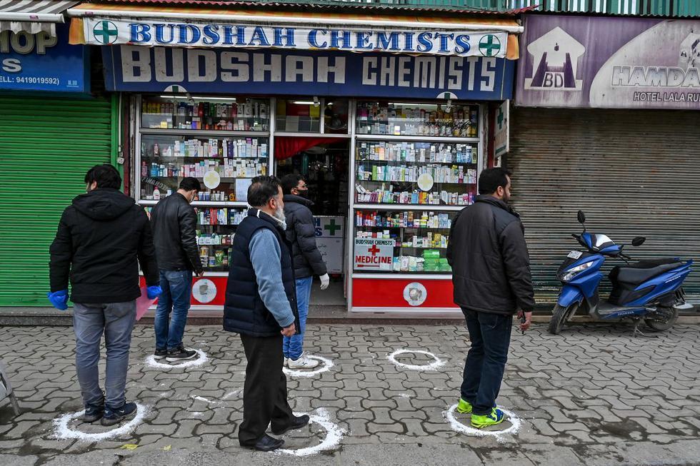 Las personas se paran en áreas designadas para mantener el distanciamiento social mientras hacen cola frente a una tienda médica durante un cierre nacional impuesto por el gobierno como medida preventiva contra el coronavirus en Srinagar. (Foto: AFP/Tauseef Mustafa)