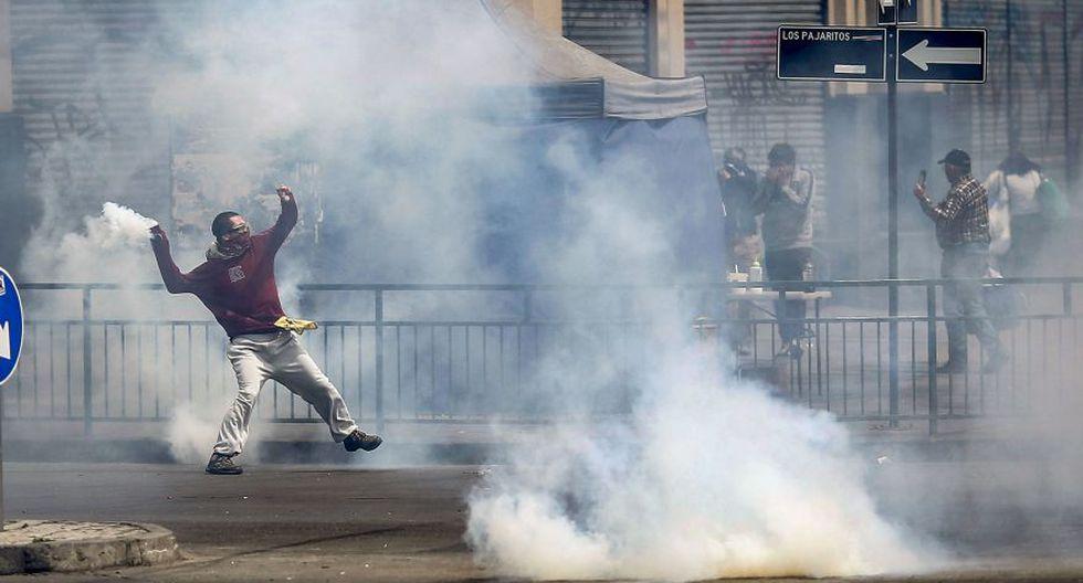 Manifestantes arrojan una lata de gas lacrimógenos. (Foto:  AFP)
