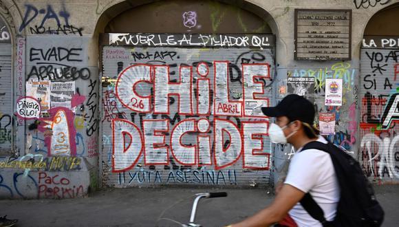 """Un hombre pasa en bicicleta frente a un muro con un graffiti que dice """"Chile decide"""" en referencia al plebiscito constitucional del domingo. (Foto de PEDRO UGARTE / AFP)."""