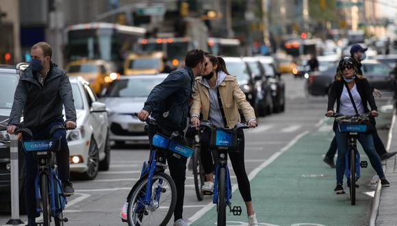 People biking down a road kiss in Manhattan, New York on April 27, 2021. - Americans vaccinated against Covid-19 no longer need to mask up outdoors when there is no crowd, President Joe Biden said, before celebrating by taking his first short walk at the White House without the face covering. (Photo by Angela Weiss / AFP)